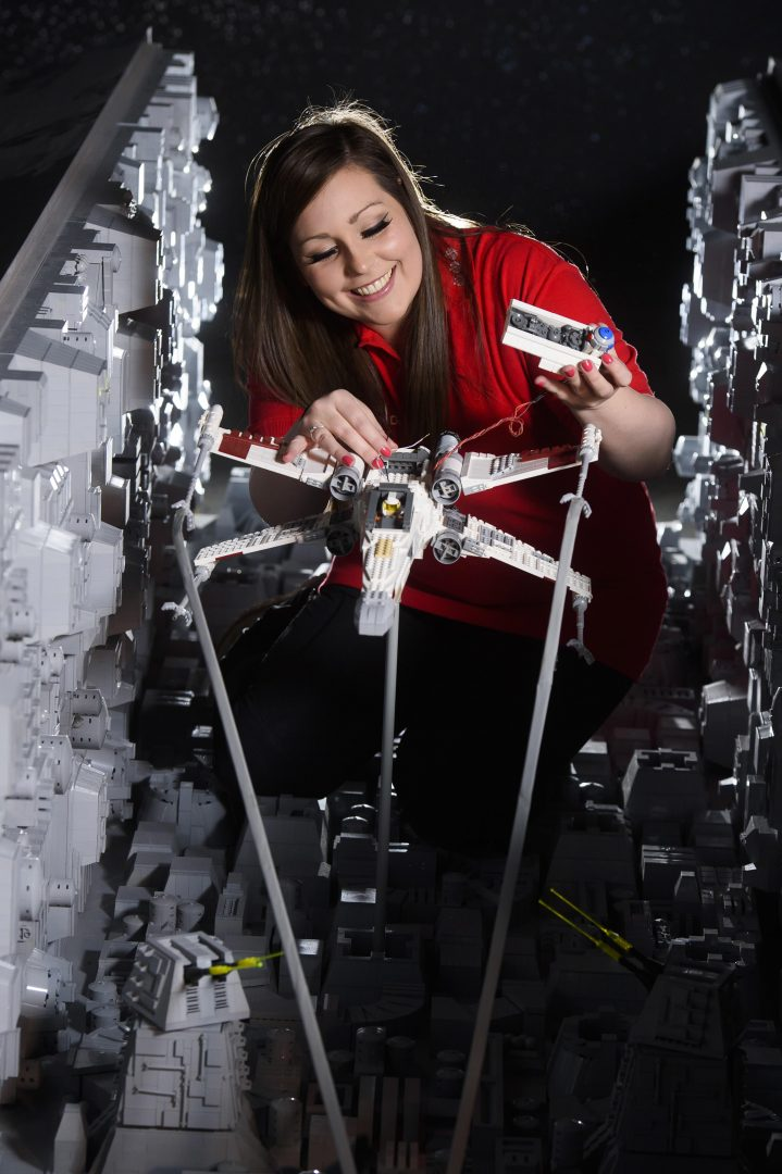 ONE OF THE WORLD'S BIGGEST EVER LEGO® STAR WARS™ MODELS INSTALLED AT THE LEGOLAND® WINDSOR RESORT. LAST PIECES PUT IN PLACE IN NEW LEGO® Star Wars™ Miniland Model Display Finale.  LEGOLAND® Model Maker, Phoebe Rumbol, puts the finishing touches to one of the Rebel Alliance ships featured in a new finale scene to the Resort's LEGO® Star Wars™ Miniland Model Display.   This is one of the smaller elements to the 651,086 brick scene and the centre piece is one of the most impressive and biggest LEGO®Star Wars™models ever created - a 500,000 brick LEGO®Star Wars™ recreation of The Death Star.   The models were installed in a mammoth operation that took three days as the massive new 2.4 metre wide, 3 metre high creation was carefully hoisted into position and the final bricks and scenes were put in place. The hefty 860kg perfectly spherical model took 15 Model Makers three months to build and guests can trigger special effects and bring the scene to life when it opens at the Resort on 11 March. TM & © Lucasfilm Ltd. All rights reserved