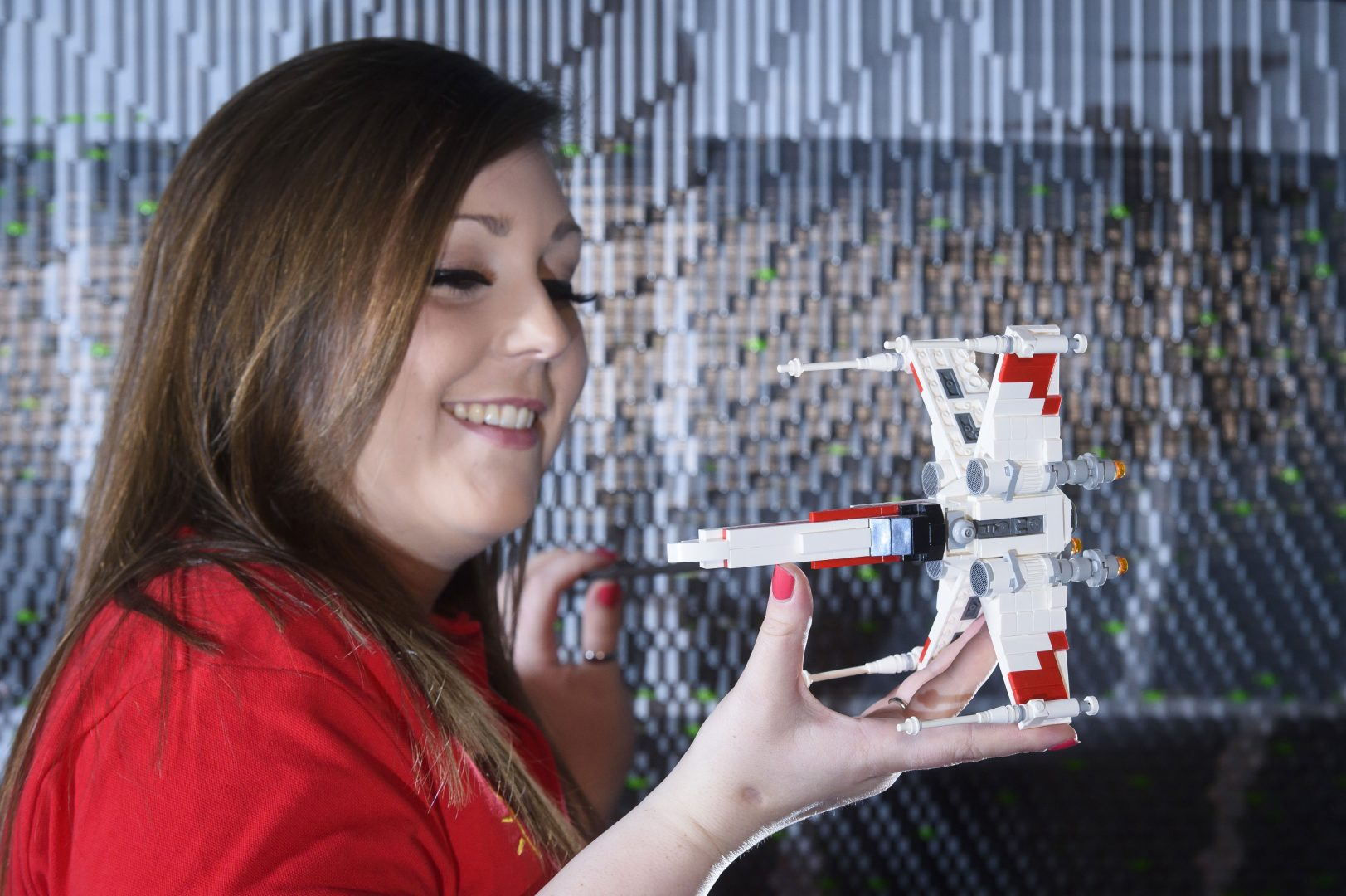 ONE OF THE WORLD'S BIGGEST EVER LEGO® STAR WARS™ MODELS INSTALLED AT THE LEGOLAND® WINDSOR RESORT. LAST PIECES PUT IN PLACE IN NEW LEGO® Star Wars™ Miniland Model Display Finale.  LEGOLAND® Model Maker Phoebe Rumbol, puts the finishing touches to some of the Rebel Alliance ships featured in a new finale scene to the Resort's LEGO® Star Wars™ Miniland Model Display. This is one of the smaller elements to the 651,086 brick scene and the centre piece is one of the most impressive and biggest LEGO® Star Wars™ models ever created - a 500,000 brick LEGO® Star Wars™ recreation of The Death Star.   The models were installed in a mammoth operation that took three days as the massive new 2.4 metre wide, 3 metre high creation was carefully hoisted into position and the final bricks and scenes were put in place. The hefty 860kg perfectly spherical model took 15 Model Makers three months to build and guests can trigger special effects and bring the scene to life when it opens at the Resort on 11 March.