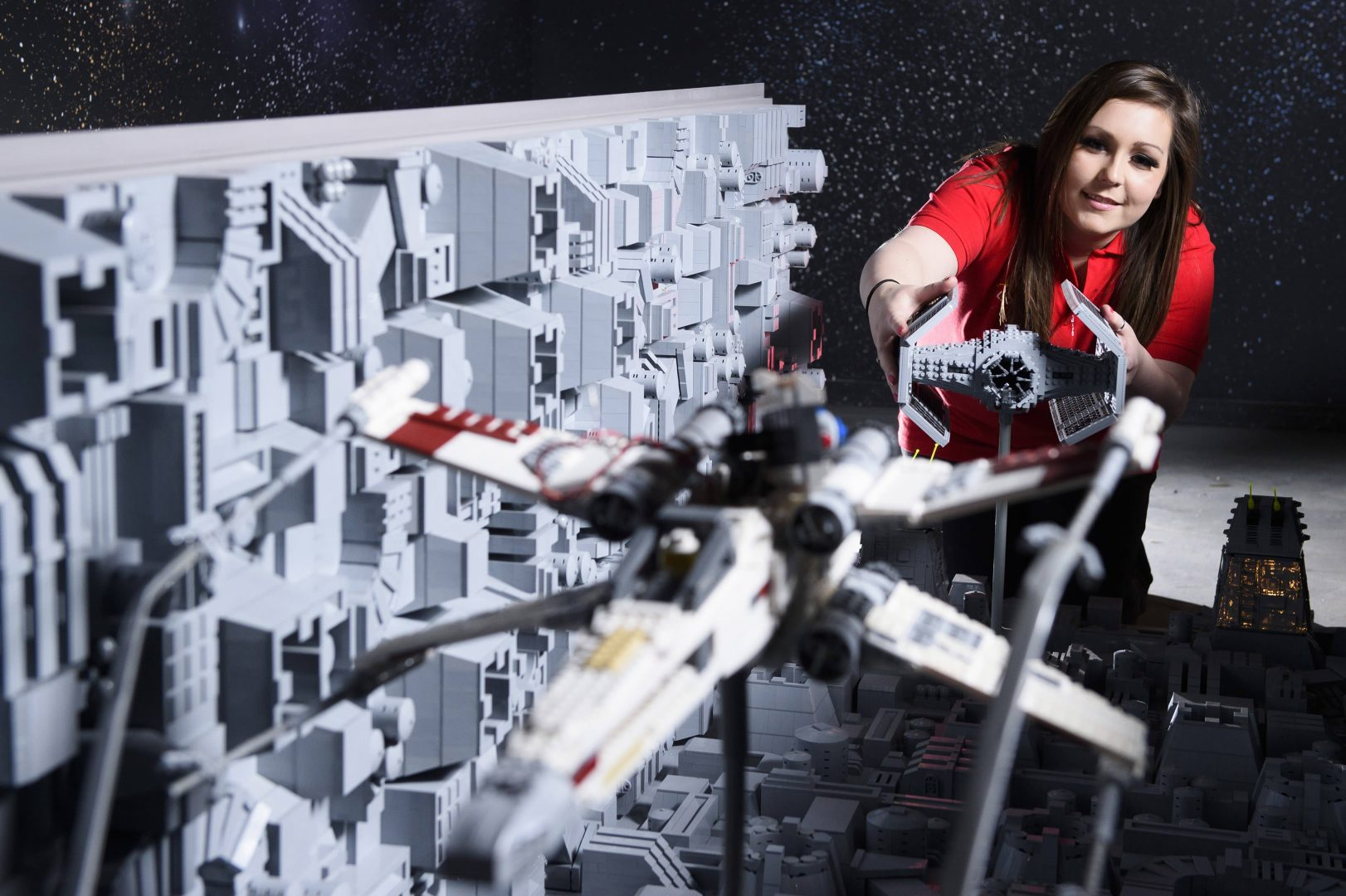 ONE OF THE WORLD'S BIGGEST EVER LEGO® STAR WARS™ MODELS INSTALLED AT THE LEGOLAND® WINDSOR RESORT. LAST PIECES PUT IN PLACE IN NEW LEGO® Star Wars™ Miniland Model Display Finale.  LEGOLAND® Model Maker Phoebe Rumbol, puts the finishing touches to some of the Rebel Alliance ships featured in a new finale scene to the Resort's LEGO® Star Wars™ Miniland Model Display. This is one of the smaller elements to the 651,086 brick scene and the centre piece is one of the most impressive and biggest LEGO® Star Wars™ models ever created - a 500,000 brick LEGO® Star Wars™ recreation of The Death Star.   The models were installed in a mammoth operation that took three days as the massive new 2.4 metre wide, 3 metre high creation was carefully hoisted into position and the final bricks and scenes were put in place. The hefty 860kg perfectly spherical model took 15 Model Makers three months to build and guests can trigger special effects and bring the scene to life when it opens at the Resort on 11 March.  TM & © Lucasfilm Ltd. All rights reserved