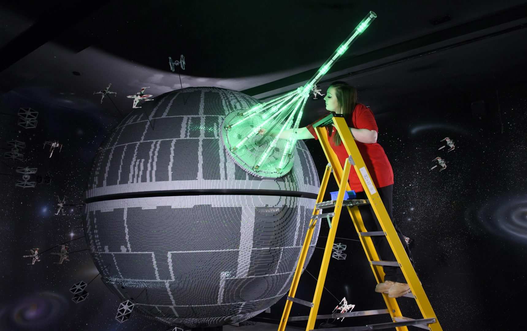 ONE OF THE WORLD'S BIGGEST EVER LEGO® STAR WARS™ MODELS INSTALLED AT THE LEGOLAND® WINDSOR RESORT. LAST PIECES PUT IN PLACE ON 500,000 LEGO® BRICK DEATH STAR. LEGOLAND® Model Maker, Phoebe Rumbol, puts the finishing touches to one of the most impressive and biggest LEGO® Star Wars™ models ever created as a 500,000 brick LEGO® Star Wars™ recreation of The Death Star is installed in a new finale to the Resort's LEGO® Star Wars™ Miniland Model Display. The operation took three days as the massive new 2.4 metre wide, 3 metre high creation was carefully hoisted into position and the final bricks  were put in place. The hefty 860kg perfectly spherical model took 15 Model Makers three months to build and  guests can trigger special effects and bring the scene to life when it opens at the Resort on 11 March.  TM & © Lucasfilm Ltd. All rights reserved