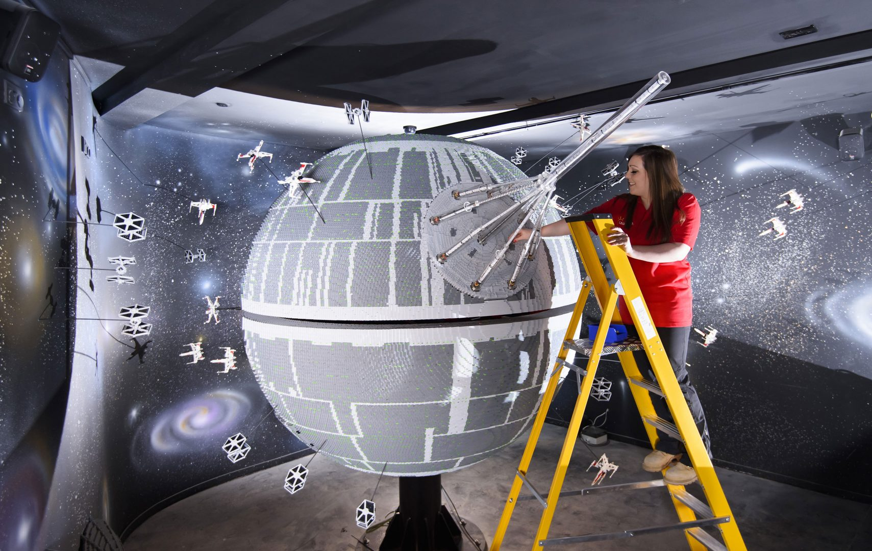 ONE OF THE WORLD'S BIGGEST EVER LEGO® STAR WARS™ MODELS INSTALLED AT THE LEGOLAND® WINDSOR RESORT. LAST PIECES PUT IN PLACE ON 500,000 LEGO® BRICK DEATH STAR. LEGOLAND® Model Maker, Phoebe Rumbol, puts the finishing touches to one of the most impressive and biggest LEGO® Star Wars™ models ever created as a 500,000 brick LEGO® Star Wars™ recreation of The Death Star is installed in a new finale to the Resort's LEGO® Star Wars™ Miniland Model Display. The operation took three days as the massive new 2.4 metre wide, 3 metre high creation was carefully hoisted into position and the final bricks  were put in place. The hefty 860kg perfectly spherical model took 15 Model Makers three months to build and  guests can trigger special effects and bring the scene to life when it opens at the Resort on 11 March.