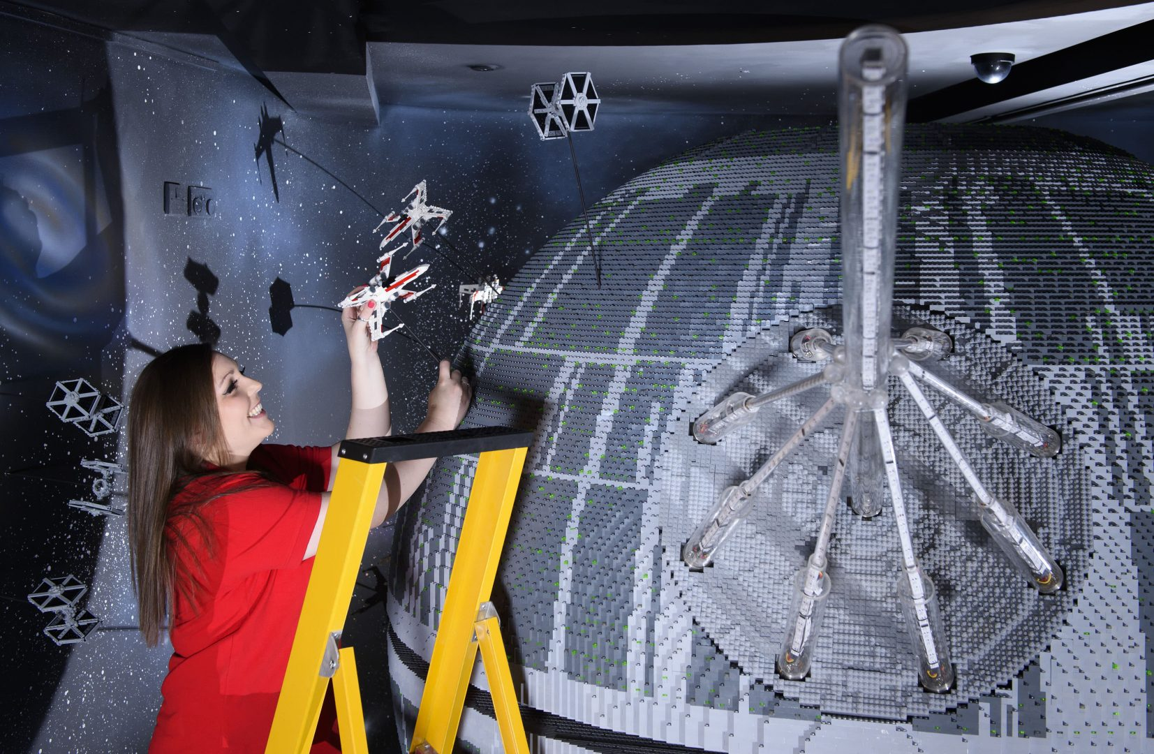 ONE OF THE WORLD'S BIGGEST EVER LEGO® STAR WARS™ MODELS INSTALLED AT THE LEGOLAND® WINDSOR RESORT.   LAST PIECES PUT IN PLACE ON 500,000 LEGO® BRICK DEATH STAR LEGOLAND® Model Maker, Phoebe Rumbol, puts the finishing touches to one of the Rebel Alliance ships featured in a new finale scene to the Resort's LEGO® Star Wars™ Miniland Model Display.  Featuring one of the most impressive and biggest LEGO® Star Wars™ models ever created - a 500,000 brick LEGO® Star Wars™ recreation of The Death Star.   The models were installed in a mammoth operation that took three days as the massive new 2.4 metre wide, 3 metre high creation was carefully hoisted into position and the final bricks and scenes were put in place. The hefty 860kg perfectly spherical model took 15 Model Makers three months to build and guests can trigger special effects and bring the scene to life when it opens at the Resort on 11 March. TM & © Lucasfilm Ltd. All rights reserved