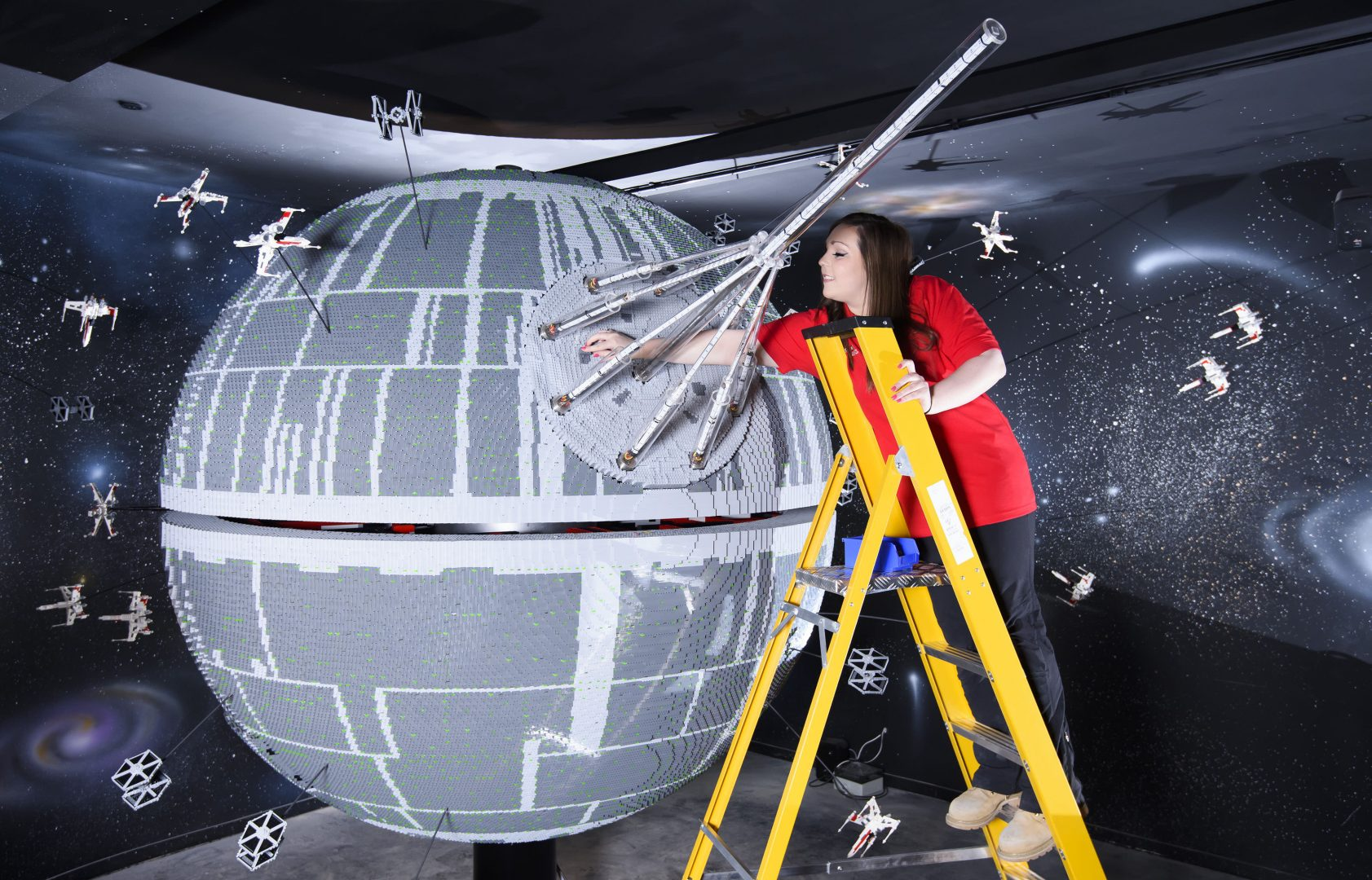 ONE OF THE WORLD'S BIGGEST EVER LEGO® STAR WARS™ MODELS INSTALLED AT THE LEGOLAND® WINDSOR RESORT.   LAST PIECES PUT IN PLACE ON 500,000 LEGO® BRICK DEATH STAR LEGOLAND® Model Maker, Phoebe Rumbol, puts the finishing touches to one of the most impressive and biggest LEGO® Star Wars™ models ever created as a 500,000 brick LEGO® Star Wars™ recreation of The Death Star is installed in a new finale to the Resort's LEGO® Star Wars™ Miniland Model Display. The operation took three days as the massive new 2.4 metre wide, 3 metre high creation was carefully hoisted into position and the final bricks  were put in place. The hefty 860kg perfectly spherical model took 15 Model Makers three months to build and  guests can trigger special effects and bring the scene to life when it opens at the Resort on 11 March.  TM & © Lucasfilm Ltd. All rights reserved